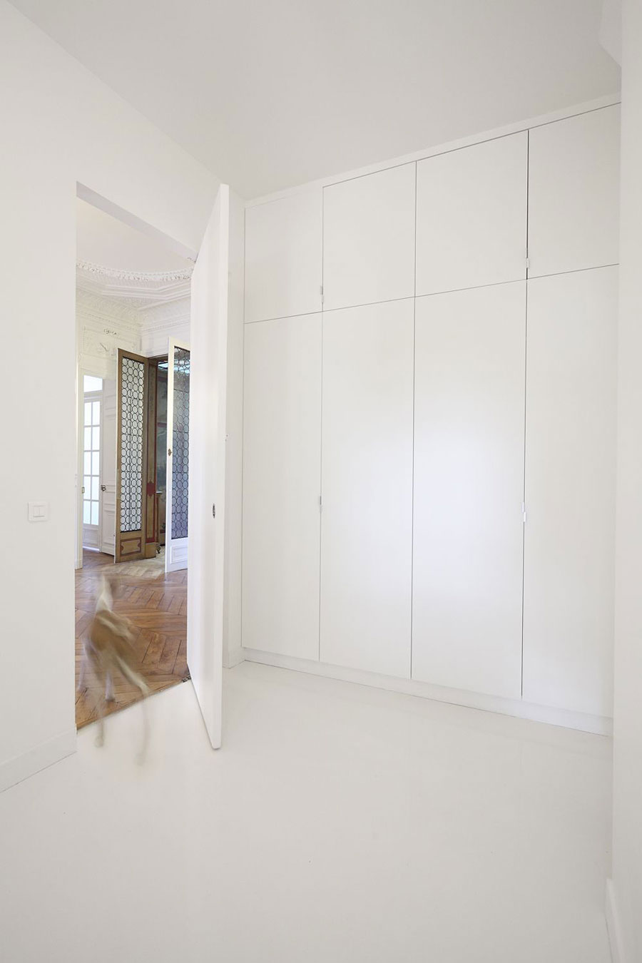 Wide White Door to the Napoleon Flat Bedroom with White Closets and White Wall on White Floor