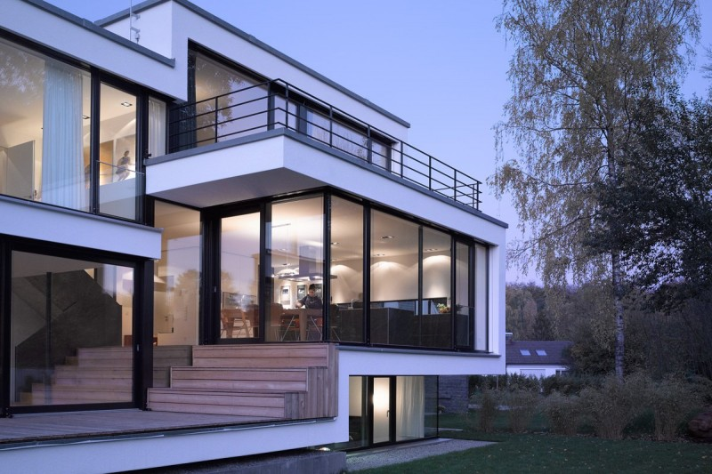 Hella View by Zochental Residence in the Left Side Showing Glass Wall and Door Design with Trees Standing the Front of House - View Modern Small House Window Design Pics