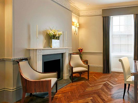 Vintage Armchairs Clamping Indoor Fireplace with Lily Flower Arrangement on Top in Living Room of Contemporary Wilton Place Townhouse