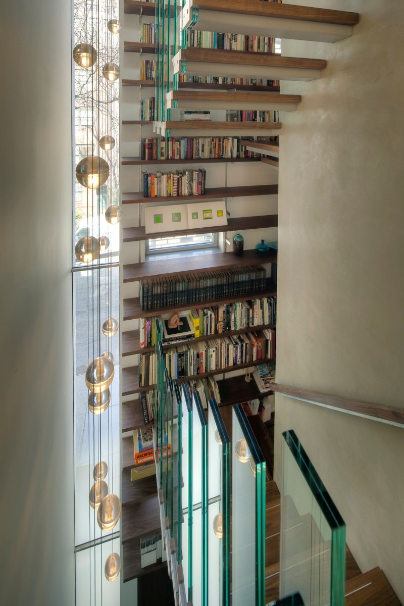 Wonderful Wooden Bookshelves near the Urban House NYC Staircase with Wooden Fooitings and the Glass Balustrade