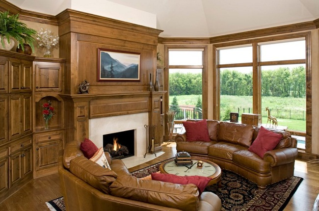 Brown Leather Curved Sofa and Wood Paneling Living Room